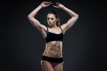 Muscular attractive fitness woman on gray background in studio