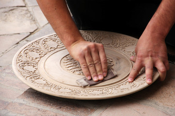 man polishes round a wooden plate with sandpaper