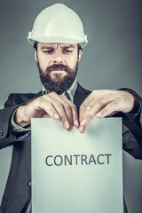 Frustrated young engineer with hardhat  tearing apart a contract