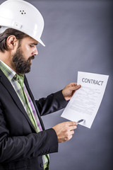 Portrait of young engineer with hardhat reading a contract
