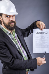 Portrait of young engineer with hardhat holding a contract