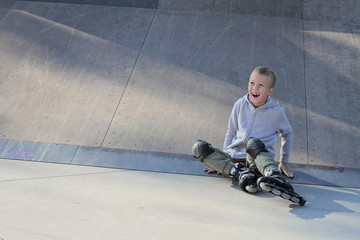 8 year old elementary school boy learn to skate on ramp in skate park. Boy falls down while roller skating. Persistence, Never give up concept.  Kids, childhood, challenge, extreme sports, excitement