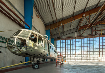 Wall Mural - Disassembled helicopter repair stand in the hangar