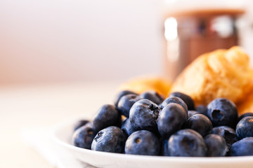 Blue blueberries and croissant close up on a purple background