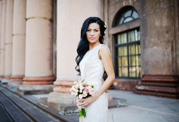 the bride with a wedding bouquet on the background of an old bui