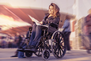 young lady in a wheelchair looking for a destination on map