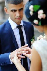 bride groom wears a wedding ring