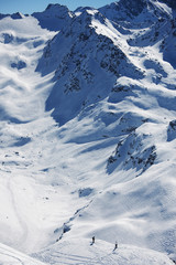 Two skiers going off piste to ski in the three valleys, France.