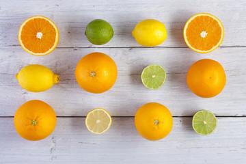 orange lemon lime shot from above on white wooden boards