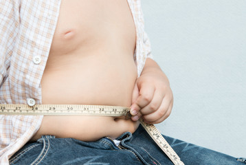 fat boy measuring his belly