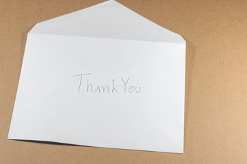 wording thank you of white envelope on brown background
