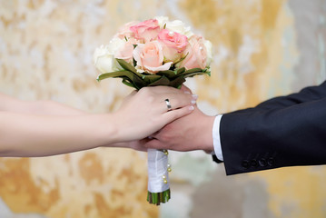 Couple hands holding a bride's bouquet