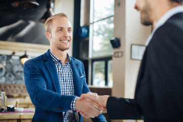 Two businessman shaking hands in a cafe