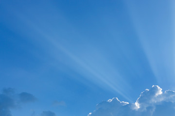 light rays of sun beam through clouds in clear blue sky