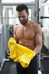 Young strong fit man in gym putting t shirt on