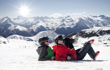 Skiers lying on snow in high mountains, Alps France
