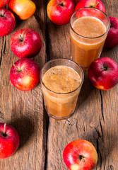 Apple juice and apples on wooden table. Nature apples