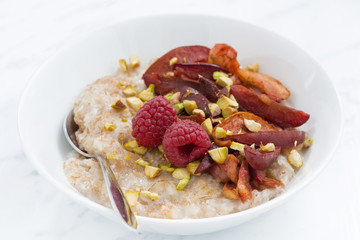 oatmeal with baked fruit on white table, closeup