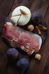 Sliced cheese with fresh figs, walnuts and ham, above view