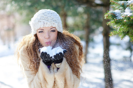 beautiful woman in winter blows snow with hands