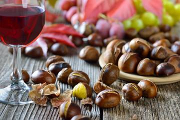 Geröstete Maroni mit neuem Rotwein, weiße und rote Weintrauben im Hintergrund