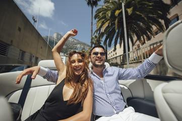 Attractive couple in a cabrio car enjoy bright sun light on vacation