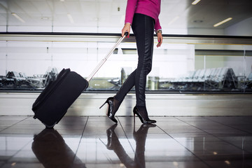 Business woman with hand luggage in airport