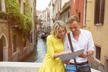Tourist couple in Venice looking at city map