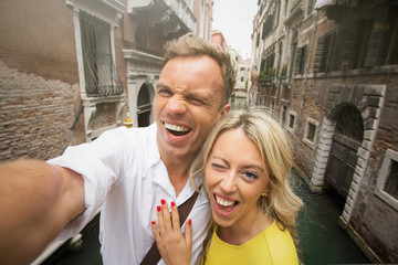 Cheerful couple taking funny selfie picture