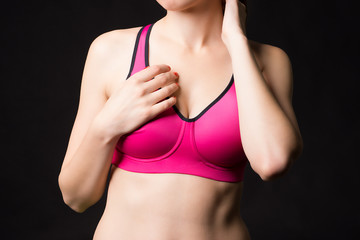 A close up of a sporty woman posing in sports pink bra with nice breast on black background.