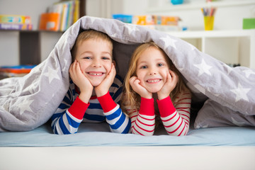 Two happy children lying under blanket