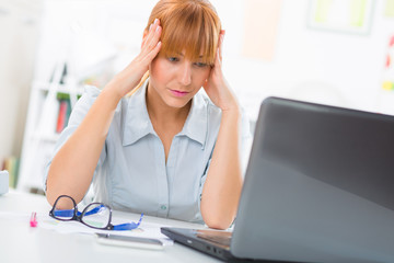 Stressed business woman sitting  her desk and looking at the laptop