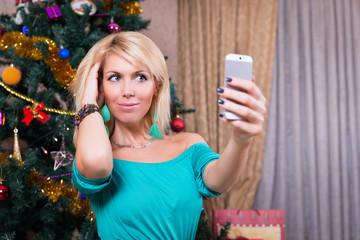 Pretty woman taking selfie photo on mobile phone near Christmas tree