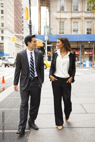 """""""A well dressed man and woman walk down a city street ..."""