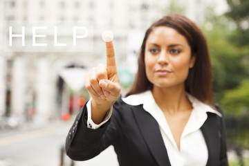 A young well dressed woman on a city street presses a virtual HELP button suspended in mid-air.