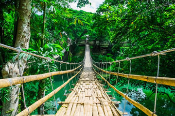 Foto auf Acrylglas Bridges Bamboo pedestrian suspension bridge over river