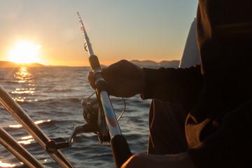 Spoed Fotobehang Vissen Man's hand with a fishing equipment in sunset
