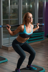 Cute sport woman in fitness room lifting empty bar