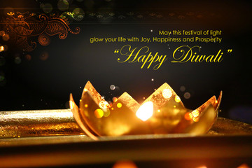 Golden lotus shaped diya on abstract Diwali background