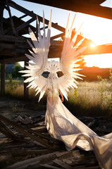 Young girl standing in demolished old building without a roof ,with lots of pillars, wearing costume, large white wings, white mask, white wig, with long white drapery
