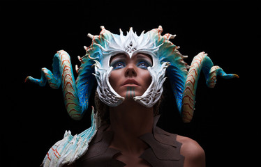 Fantasy concept of a young girl,strong brave warrior,wearing a helmet - mask with horns on head with corals with dots