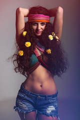 Young hippie girl  with long, brown, curly hair,  wearing colorful scarf around forehead ,her hand is behind head, wearing colorful top over her breasts, seductively smileing