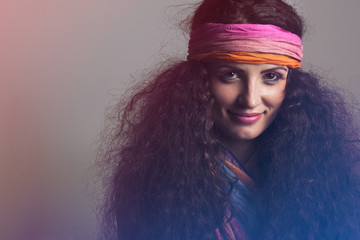 portrait of a young hippie girl  with long, brown, curly hair,  wearing colorful scarf around forehead ,her hand is behind head, wearing colorful top over her breasts, seductively smileing