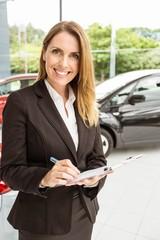 Smiling saleswoman checking a car