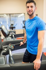 Smiling man standing on a treadmill
