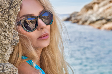 The very beautiful blond hair sexy woman girl is standing in the erotic blue swimsuit lingerie wearing sunglasses on the rocks