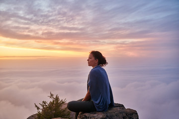 Woman sitting serenely on a mountain top in early morning