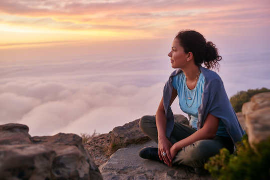 Woman looking out at the morning clouds from a mountain top