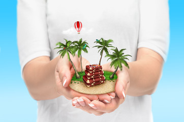 Small fantastic island with palms and suitcase in women's hands.