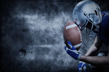 Composite image of american football player with ball against helmet
